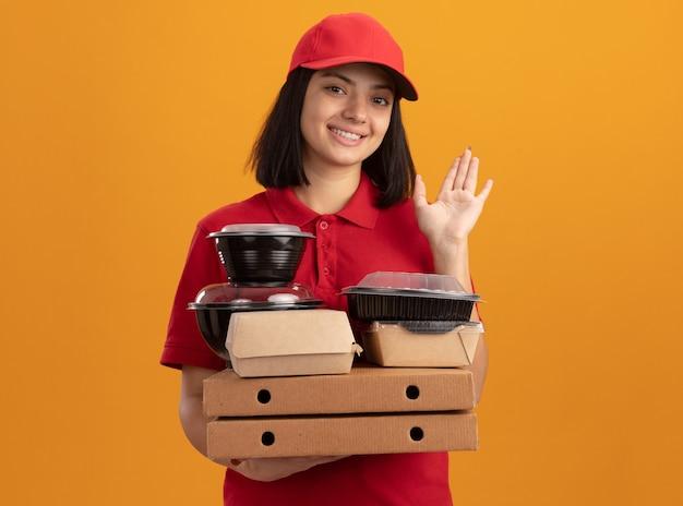 Jong bezorgmeisje in blauw uniform en pet met pizzadozen en voedselpakket glimlachend gelukkig en positief golvend met hand staande over oranje muur