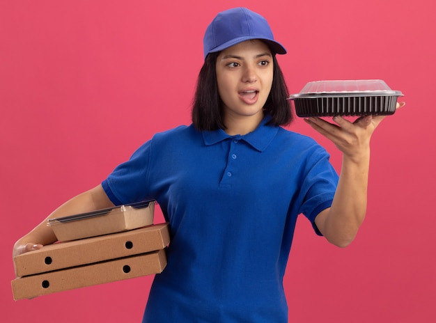 Jong bezorgmeisje in blauw uniform en pet met pizzadozen en voedselpakket kijken pakket verrast en verbaasd staande over roze muur