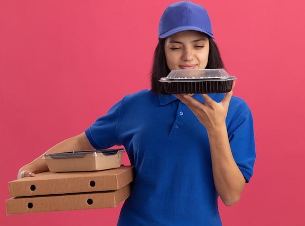 Jong bezorgmeisje in blauw uniform en pet met pizzadozen en voedselpakket op zoek zelfverzekerd en gelukkig staande over roze muur