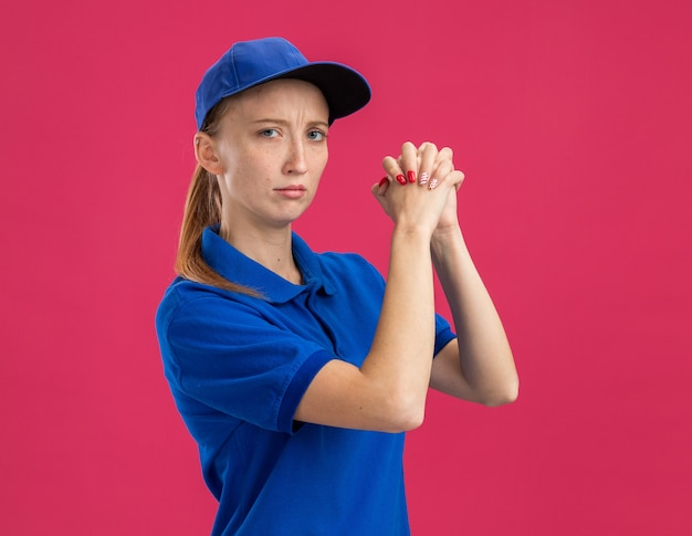 Jong bezorgmeisje in blauw uniform en pet met serieuze zelfverzekerde uitdrukking die handen bij elkaar houdt en teamwerkgebaar maakt over roze muur