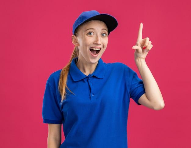 Jong bezorgmeisje in blauw uniform en pet verrast en blij dat wijsvinger een nieuw idee heeft dat over een roze muur staat