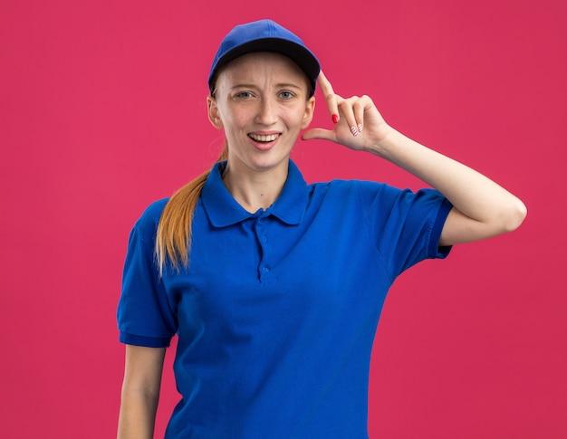 Jong bezorgmeisje in blauw uniform en pet verward met hand op haar hoofd die over roze muur staat