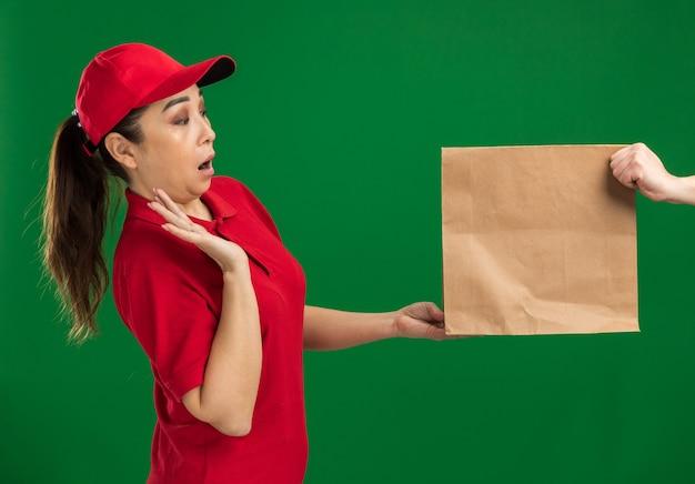 Jong bezorgmeisje in rood uniform en pet die weigert een papieren pakket te ontvangen en er verbaasd naar kijkt terwijl ze over de groene muur staat