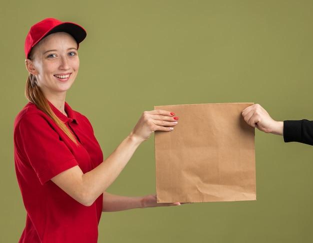 Jong bezorgmeisje in rood uniform en pet met papieren pakket en geeft het aan een klant die zelfverzekerd over groene muur glimlacht