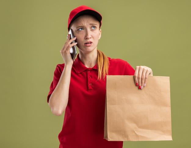 Jong bezorgmeisje in rood uniform en pet met papieren pakketje dat er verward uitziet terwijl ze op mobiele telefoon over groene muur praat
