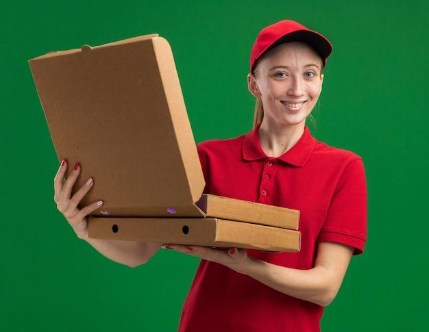 Jong bezorgmeisje in rood uniform en pet met pizzadozen die een van hen glimlachend vriendelijk over groene muur openen