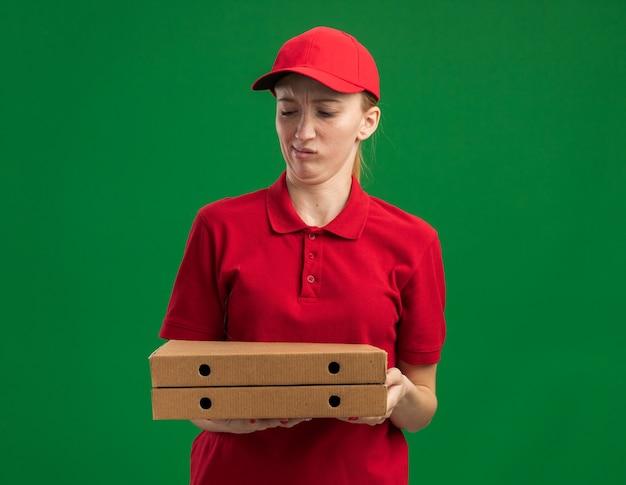 Jong bezorgmeisje in rood uniform en pet met pizzadozen die verward en ontevreden naar ze kijken terwijl ze over de groene muur staan