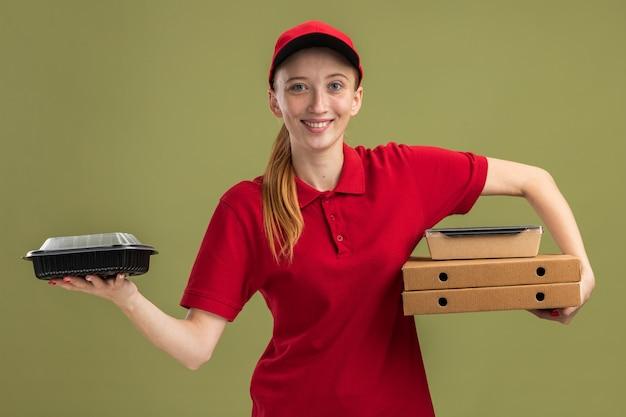Jong bezorgmeisje in rood uniform en pet met pizzadozen en voedselpakketten die zelfverzekerd over groene muur glimlachen