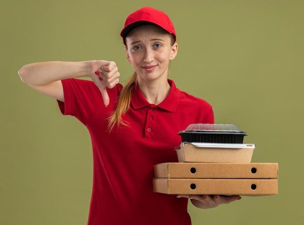 Jong bezorgmeisje in rood uniform en pet met pizzadozen en voedselpakketten glimlachend met duimen naar beneden over groene muur