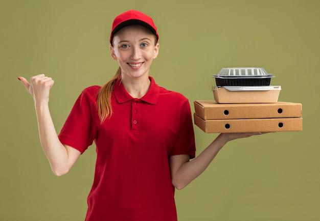 Jong bezorgmeisje in rood uniform en pet met pizzadozen en voedselpakketten glimlachend zelfverzekerd wijzend naar de zijkant over groene muur