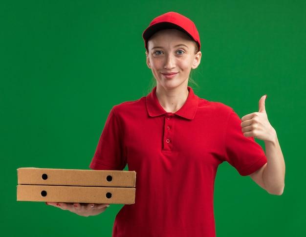 Jong bezorgmeisje in rood uniform en pet met pizzadozen glimlachend zelfverzekerd en duimen omhoog terwijl ze over groene muur staan