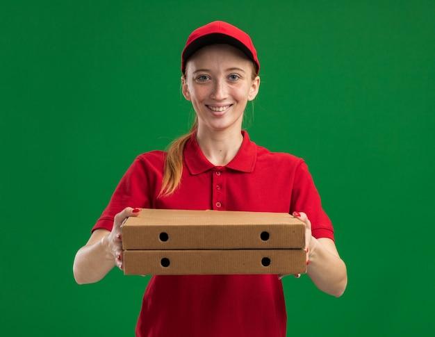 Jong bezorgmeisje in rood uniform en pet met pizzadozen glimlachend zelfverzekerd met een blij gezicht dat over de groene muur staat