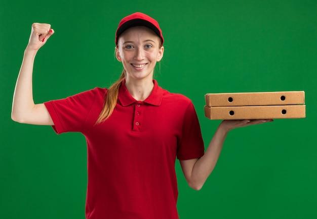 Jong bezorgmeisje in rood uniform en pet met pizzadozen glimlachend zelfverzekerd met opgeheven vuist over groene muur