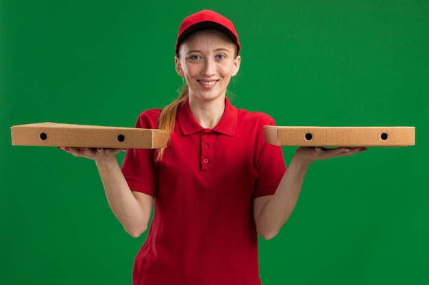 Jong bezorgmeisje in rood uniform en pet met pizzadozen met een glimlach op een blij gezicht dat over een groene muur staat