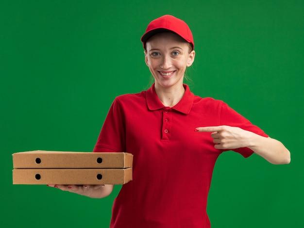 Jong bezorgmeisje in rood uniform en pet met pizzadozen wijzend met wijsvinger naar hen glimlachend zelfverzekerd over groene muur