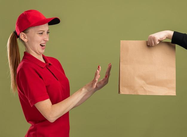 Jong bezorgmeisje in rood uniform en pet weigert papieren pakket te ontvangen