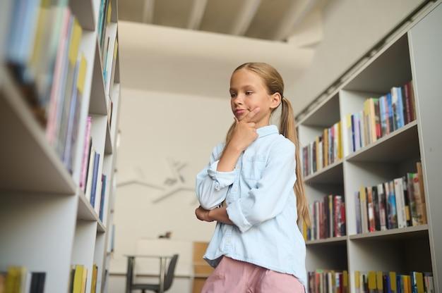 Jong blank meisje concentreerde zich op het kiezen van schoolboeken