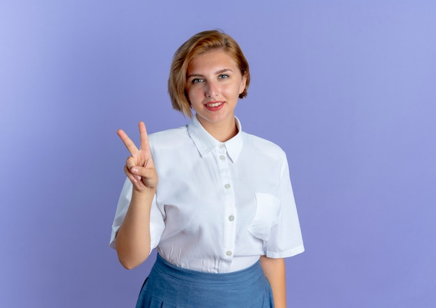 Jong blij blond russisch meisje gebaren overwinning handteken