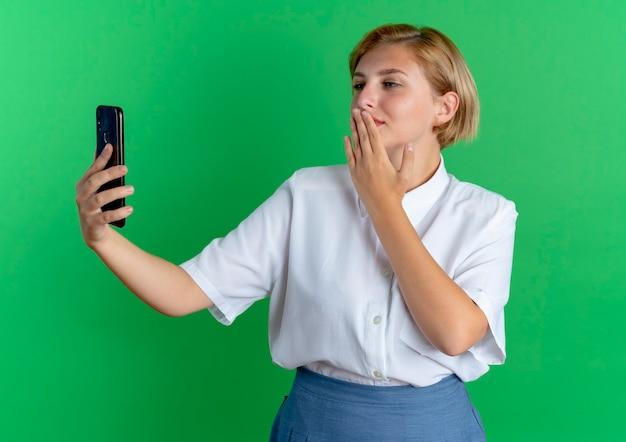 Jong blij blond russisch meisje houdt en kijkt naar telefoon verzendende kus met hand geïsoleerd op groene achtergrond met kopie ruimte