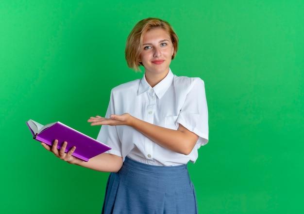 Jong blij blond russisch meisje houdt en wijst op boek
