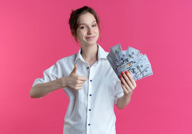 Jong blij blond russisch meisje houdt en wijst op geld