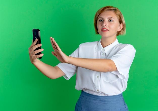 Jong blij blond russisch meisje houdt telefoon met opgeheven hand en kijkt naar kant geïsoleerd op groene achtergrond met kopie ruimte
