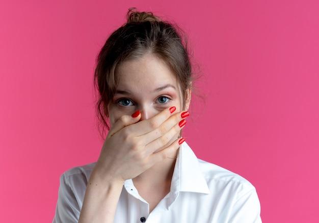 Jong blij blond russisch meisje legt hand op mond camera kijken