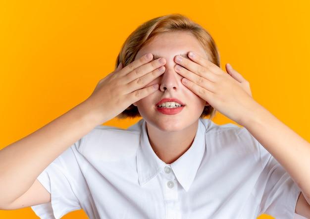 Jong blij blond russisch meisje sluit ogen met handen geïsoleerd op een oranje achtergrond met kopie ruimte