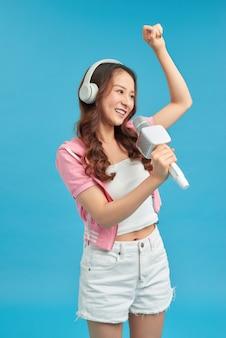 Jong blij en opgewonden aziatisch meisje dat online karaoke-nummer zingt met microfoon en springt