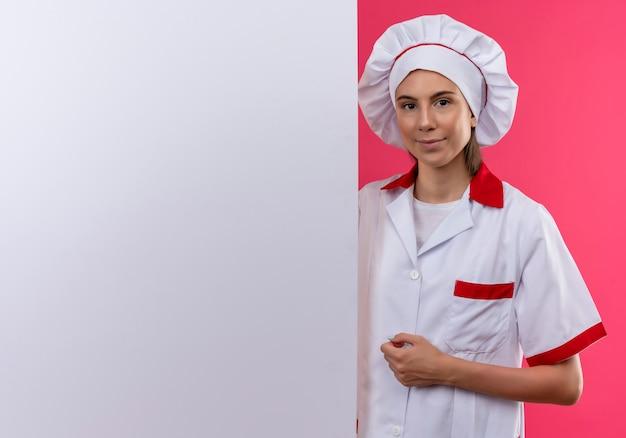 Jong blij kaukasisch kokmeisje in eenvormige chef-kok bevindt zich achter witte muur op roze met exemplaarruimte