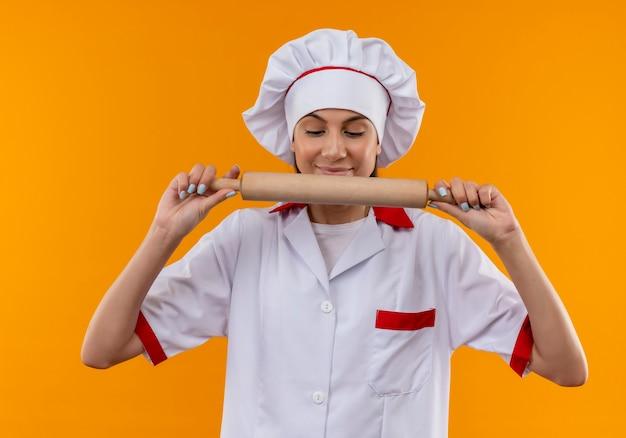 Jong blij kaukasisch kokmeisje in eenvormige chef-kok houdt en kijkt naar deegroller die op oranje ruimte met exemplaarruimte wordt geïsoleerd
