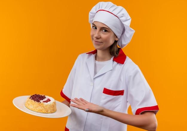Jong blij kaukasisch kokmeisje in eenvormige chef-kok houdt en wijst op cake op plaat die op oranje achtergrond met exemplaarruimte wordt geïsoleerd
