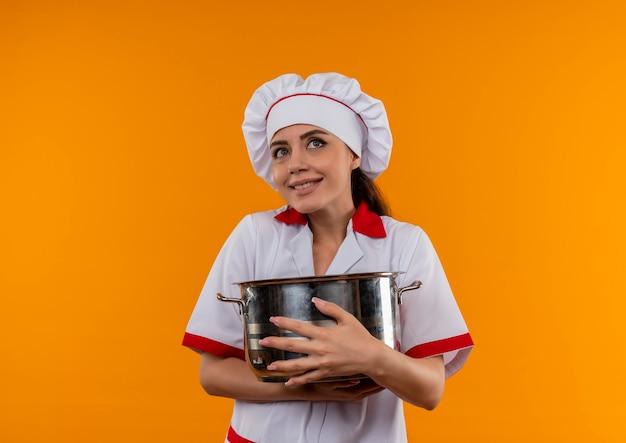 Jong blij kaukasisch kokmeisje in eenvormige chef-kok koestert pot en kijkt omhoog geïsoleerd op oranje muur met exemplaarruimte