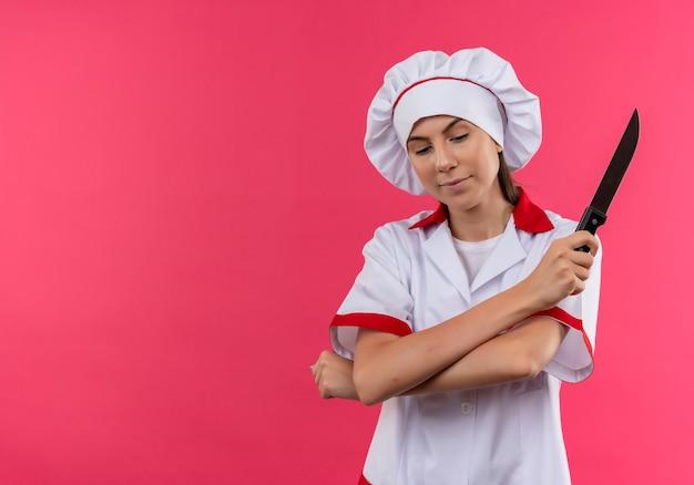 Jong blij kaukasisch kokmeisje in eenvormige chef-kok kruist wapens en houdt mes dat op roze achtergrond met exemplaarruimte wordt geïsoleerd