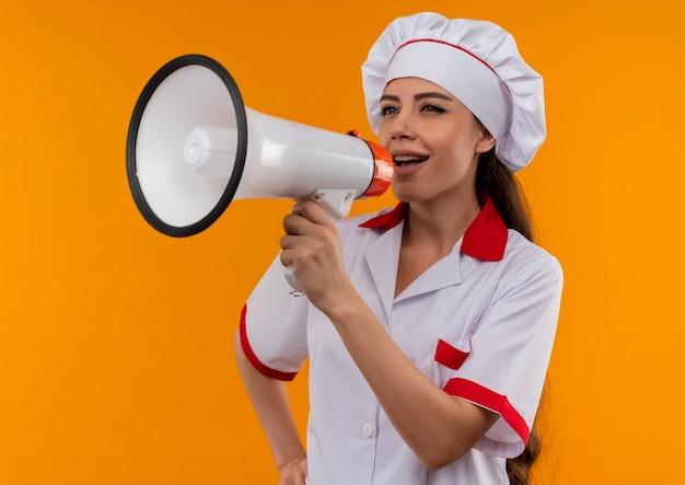 Jong blij kaukasisch kokmeisje in eenvormige chef-kok schreeuwt door luide spreker die op oranje muur met exemplaarruimte wordt geïsoleerd