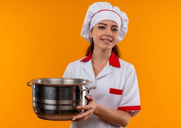 Jong blij kaukasisch kokmeisje in uniform chef-kok houdt pot en kijkt naar camera geïsoleerd op oranje muur met kopie ruimte