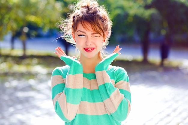 Jong blij lachend tienermeisje knipoogt naar je, positieve mod en emoties hebben, lichte comfortabele casual trui dragen, poseren in het park op mooie zonnige dag.