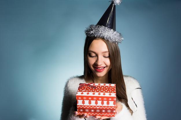 Jong blij meisje kreeg cadeau voor nieuwe voet van collega's, op haar hoofd een feestelijke pet