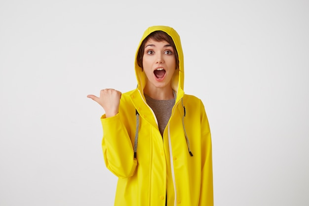 Jong blij verbaasd schattig kortharig meisje draagt een gele regenjas, met wijd open mond en ogen, wil je aandacht trekken en wijst naar kopie ruimte aan de linkerkant, staat over een witte muur.