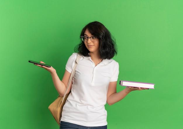 Jong blij vrij kaukasisch schoolmeisje die glazen en achterzak dragen houdt boek en telefoon op groen met exemplaarruimte