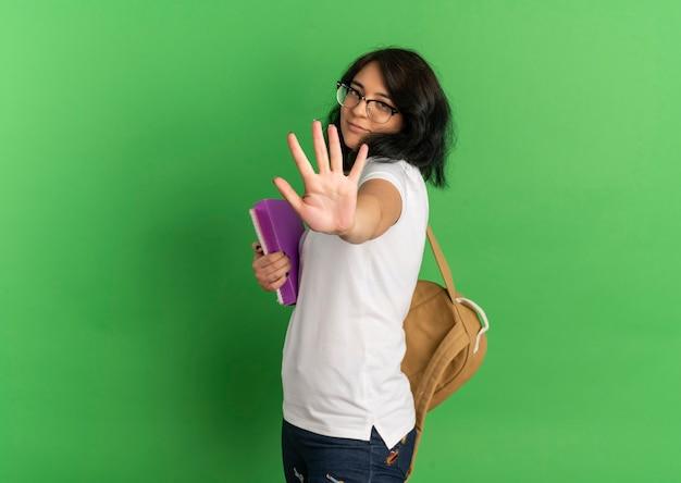 Jong blij vrij kaukasisch schoolmeisje met bril en rugtas gebaren stoppen handteken houden boeken geïsoleerd op groene ruimte met kopie ruimte