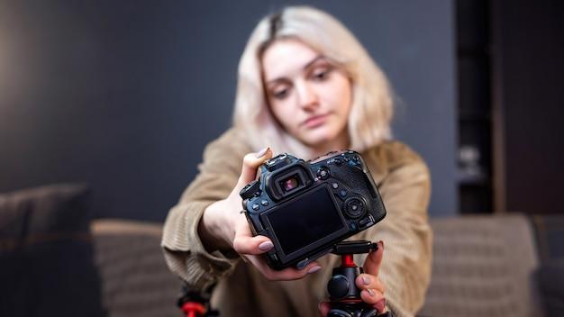Jong blond lachend meisje dat een camera op een statief zet. werken vanuit huis. beginnen met het filmen van vlog