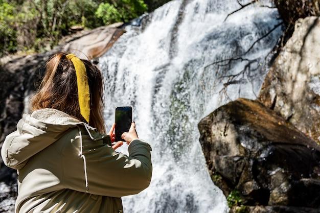 Jong blond meisje dat een foto neemt met haar mobiele telefoon bij de waterval van las nogaledas, extremadura, spanje.