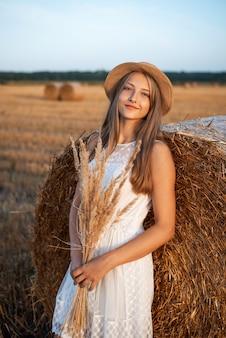 Jong blond meisje dat op de baal stro leunt en een boeket van droge bloemen houdt