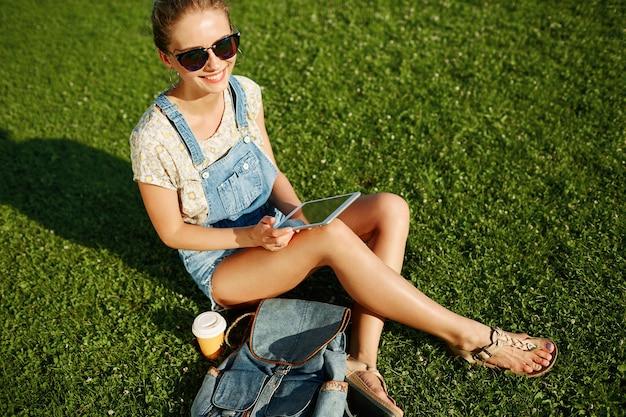 Jong blond meisje met behulp van tablet buiten zittend op het gras