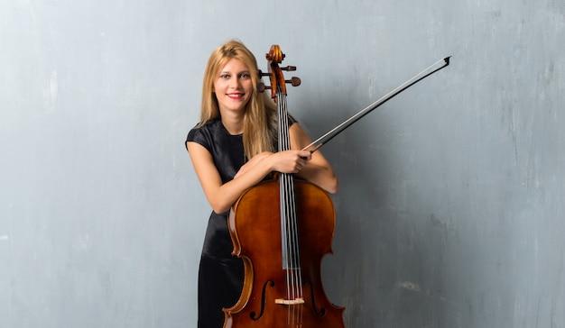Jong blond meisje met haar cello op gestructureerde muur achtergrond