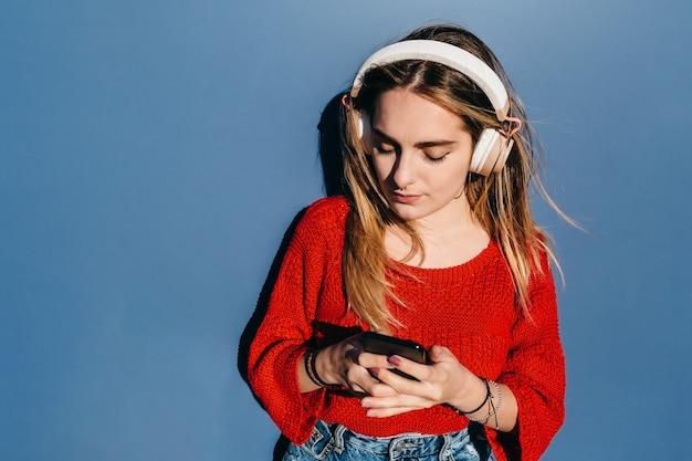 Jong blond meisje met koptelefoon op het kijken naar haar mobiel op blauwe achtergrond