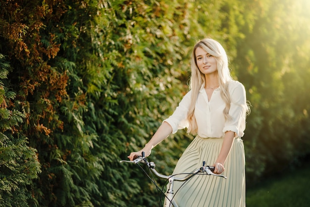 Jong blond meisje met lang haar dat zich dichtbij uitstekende witte fiets bevindt.