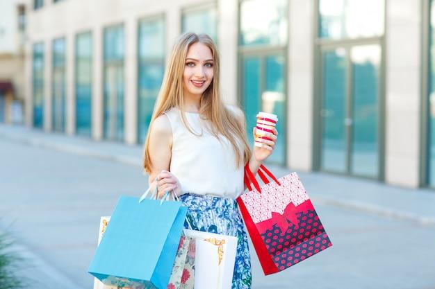 Jong blond meisje van het levensstijlportret, met het winkelen zakken die van winkel opstappen.