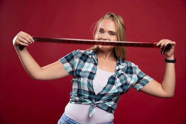 Jong blond model dat plezier heeft terwijl ze een polaroidfilm vasthoudt.